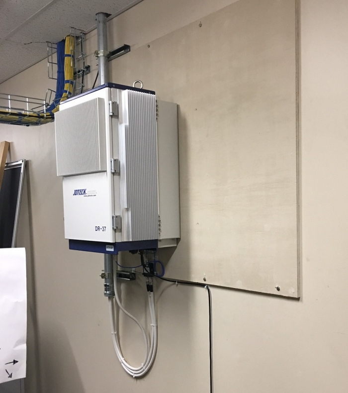 Quad Band Digital Repeater installed in communications room of customer's site. IP66 rated enclosure with built-In cooling fans.