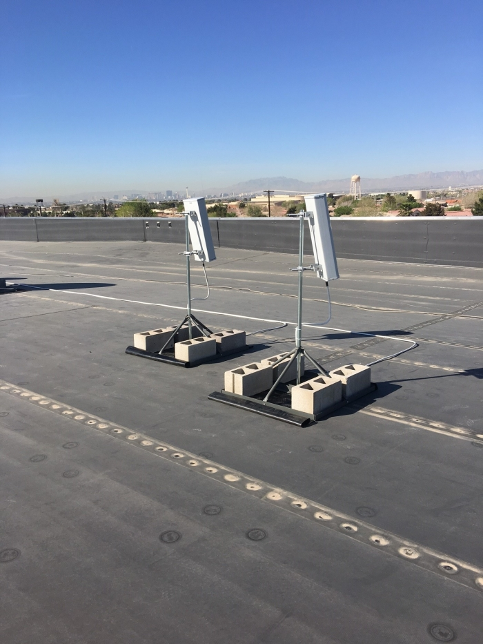Pair of sector antennas installed on roof of building. Dual antennas ensures a good lock on the azimuth for the carriers that need to be supported.